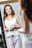 smiling young woman measuring her waistline and looking at mirror
