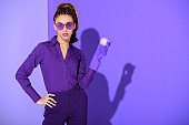 stylish african american girl in rubber glove holding purple apple, ultra violet trend of 2018 year