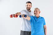 portrait of smiling rehabilitation therapist and senior man exercising with dumbbells isolated on grey
