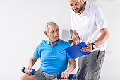 rehabilitation therapist with notepad assisting senior man exercising with dumbbells on grey backdrop