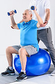 cropped shot of rehabilitation therapist assisting senior man exercising with dumbbells on fitness ball isolated on grey