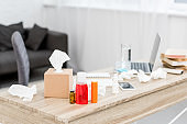 close-up shot of messy office workplace with laptop and various medicines and paper napkins