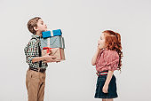 side view of boy presenting gifts to shocked little girl isolated on grey