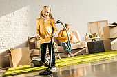 smiling little child cleaning room with vacuum cleaner while mother reading book on sofa after relocation
