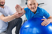 partial view of rehabilitation therapist assisting smiling senior man exercising on fitness ball