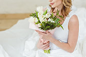 cropped view of woman with bouquet of flowers for international womens day