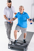 rehabilitation therapist assisting senior man exercising with dumbbells on stepper on grey backdrop