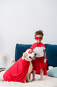 Cute little african american kid with happy dog in red superhero costumes standing on the bed