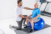 rehabilitation therapist assisting senior man exercising on fitness ball