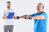 portrait of rehabilitation therapist with notepad assisting senior man exercising with dumbbells isolated on grey