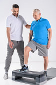 rehabilitation therapist helping senior man exercising on stepper isolated on grey