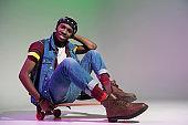 african american man sitting on skateboard