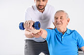 selective focus of rehabilitation therapist assisting senior man exercising with dumbbell isolated on grey