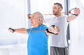 selective focus of rehabilitation therapist and senior man exercising with rubber tapes
