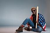 man with us flag on shoulders holding baseball bat