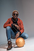 man sitting with basketball ball on floor