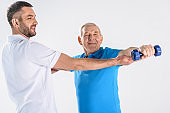portrait of rehabilitation therapist assisting senior man exercising with dumbbell isolated on grey