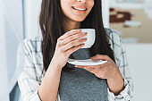 Smiling african american woman drinking coffee from white cup