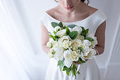 cropped view of bride holding wedding bouquet