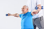 partial view of rehabilitation therapist assisting senior man exercising with dumbbells on grey background
