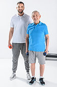 rehabilitation therapist and senior man with dumbbells looking at camera on grey background