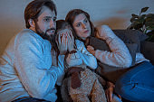 parents and daughter watching horror movie in evening at home