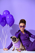 smiling african american girl posing with purple balloons and pug, ultra violet trend