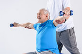 cropped shot of rehabilitation therapist assisting senior man exercising with dumbbells on grey backdrop