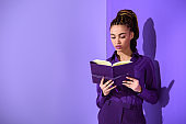 stylish mulatto girl reading diary, ultra violet trend of 2018 year
