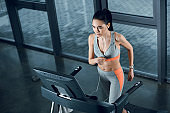 high angle view of young athletic sportswoman running on treadmill at gym