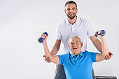 portrait of smiling rehabilitation therapist assisting senior man exercising with dumbbells isolated on grey