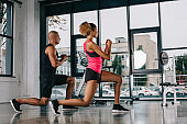 side view of young african american couple of athletes exercising at gym