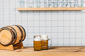selective focus of beer barrel and two mugs with light beer at bar counter