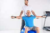 rehabilitation therapist assisting senior man exercising with rubber tape on fitness ball on grey backdrop