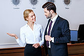 smiling receptionist pointing on something to businessman