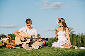 handsome groom playing on acoustic guitar for bride with wine during romantic picnic