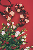 top view of gift boxes and beautiful eustoma flowers on red