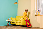pensive young woman in retro clothing sitting on yellow sofa at colorful apartment, doll house concept