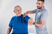 portrait of physiotherapist doing massage to smiling senior man on massage table