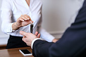 cropped image of receptionist giving key to customer in hotel