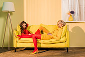 retro styled beautiful girls in colorful dresses lying on sofa and looking at camera at home