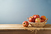 Red apples in basket on wooden kitchen table background