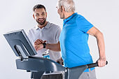 smiling rehabilitation therapist assisting senior man exercising on treadmill isolated on grey