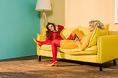 retro styled beautiful girls in colorful dresses lying on sofa and looking away at home