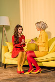 retro styled beautiful girls in colorful dresses playing rock paper scissors game on sofa at home