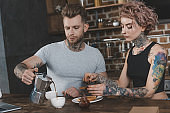 tattooed couple eating toasts and drinking coffee for breakfast