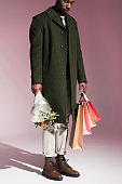man holding bouquet of flowers and bright shopping bags