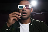 shocked african american man in 3d glasses watching movie in cinema