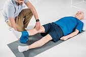 partial view of rehabilitation therapist assisting senior man exercising with rubber tape on mat