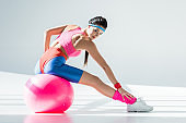 beautiful athletic girl sitting and exercising on fitness ball on grey